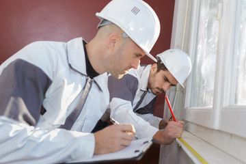 Workmen measuring window
