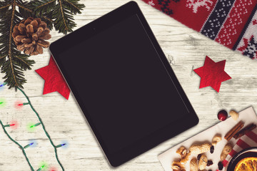 Tablet on a wooden table, christmas scene