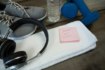 Shoes, headphones, water bottle, towel, dumbbell and stick notes
