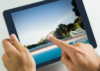Hand touching tablet with swimming pool