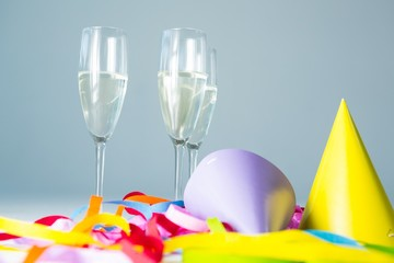 Champagne flutes with party hat and streamers