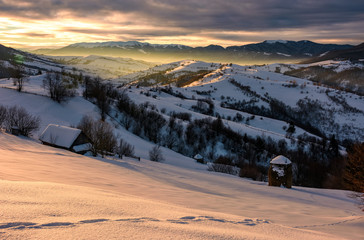 beautiful mountainous countryside at sunrise. rural area with sheds and haystacks on snow cowered forested hills of Carpathian mountains