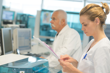 female doctor checking a medical report and colleagues standing behind