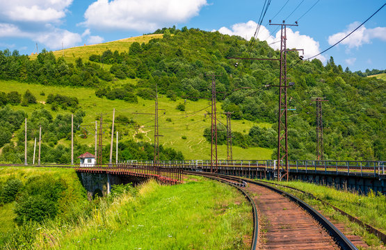 railroad viaduct through forested hills in summer. lovely transportation scenery in Carpathian mountains, Skotars'ke, Ukraine