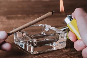 Cannabis Joint wird mit Feuerzeug angezündet