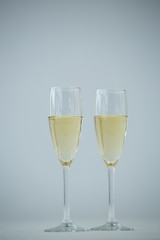 Two champagne flutes against white background