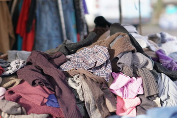 Stack of colourful clothes and textiles at market stall