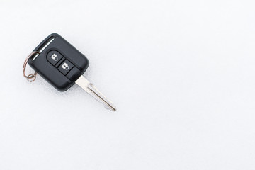 A black car key lies on the snow.