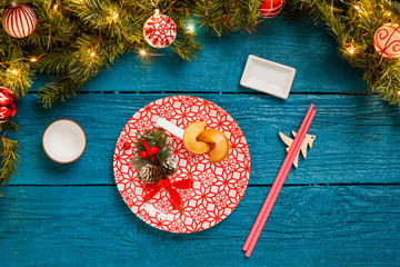 Photo of Christmas branches of pine, sushi sticks, prediction cookies, plates with red pattern