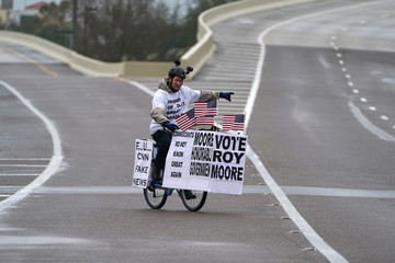 A man rides his bike with signs of support for Alabama Republican senatorial candidate Roy Moore around a venue that will host U.S. President Donald Trump later in the day in Pensacola, Florida