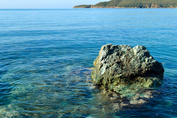 Sea coast. A calm sea without waves. A large boulder. Transparent waters of the sea. Adriatic