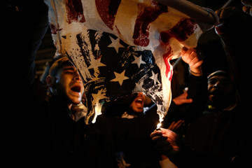 People Burn a t-shirt depicting an American flag during a protest against Donald Trump's decision to recognize Jerusalem as the capital of Israel,outside the U.S. Embassy in Athens