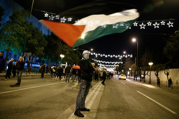 A demonstrator waves a Palestinian flag during a protest against Donald Trump's decision to recognise Jerusalem as the capital of Israel, in Athens