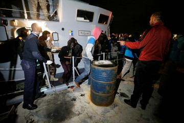 Migrants arrive at a naval base after they were rescued by Libyan coast guards in Tripoli