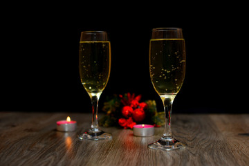 glasses of champagne and Christmas ornaments on dark wooden background