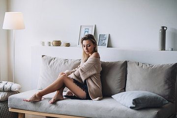 Beautiful white stylish woman with long nacked legs in cozy scandinavian interrior sits at home, portrait of the beautiful girl, fashion portraits