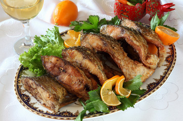 Fried fish-a carp on a plate decorated with greens with lemon and white wine.