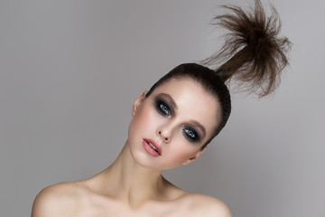 A young girl with bright makeup and radiant skin. Creative hairstyle on the head. On a gray background.
