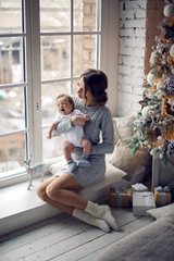mother with newborn son sitting next to the Christmas tree