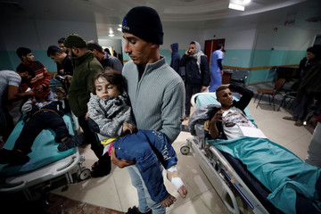 Palestinian man carries his wounded daughter as she waits to receive treatment following Israeli airstrikes on nearby militant targets, at a hospital in the northern Gaza Strip
