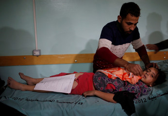 A man tends to a wounded Palestinian girl following Israeli airstrikes on nearby militant targets, at a hospital in the northern Gaza Strip