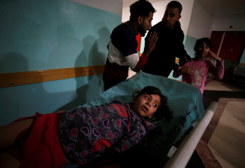 A wounded Palestinian girl lies on a bed following Israeli airstrikes on nearby militant targets, at a hospital in the northern Gaza Strip