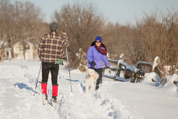A man and a woman with a dog greet each other while enjoying snow after the first lake-effect snowfall of the season at Knox Farm State Park in the Buffalo suburb of East Aurora