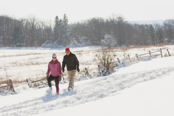 A woman and a man snowshoe after the first lake-effect snowfall of the season at Knox Farm State Park in the Buffalo suburb of East Aurora