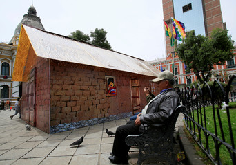 """A man sits next to a replica of the house where Bolivia's President Evo Morales was born, as it is presented by the government as """"The House of Desires"""", during the Christmas season at the Murillo square in La Paz"""