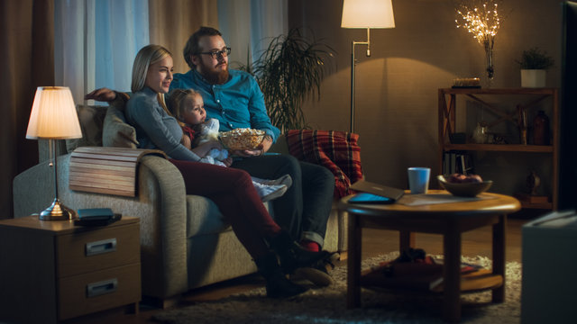 Long Shot of a Father, Mother and Little Girl Watching TV. They Sit on a Sofa in Their Cozy Living Room and Eat Popcorn. It's Evening.