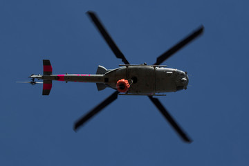 An U.S. military helicopter from Camp Pendleton makes a water drop on a hotspot caused by the Lilac Fire, a fast moving wildfire in Bonsall, California