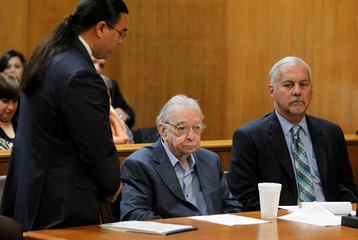 Former priest John Feit listens to his attorney as he decides not to testify during the sentencing phase of his trial for the 1960 murder of Garza in Edinburg