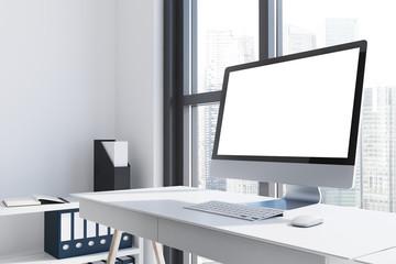 White computer screen on a white desk