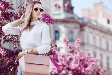 Outdoor portrait of young beautiful girl posing in street of european city, blooming trees on background. Model wearing stylish sunglasses, holding pink bag. Female fashion concept. Copy, empty space Wall mural