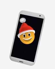 Emoticon mit Weihnachtsmütze schaut aus dem Display eines Handys