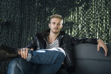 Portrait of Casual Young Man Sitting in Backyard Couch