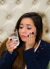 Drunk woman holding a glass of water in the bed after a party and touching her face using her hand, hangover concept