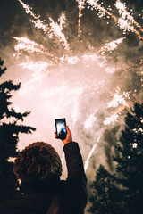 Woman taking photos of fireworks using smartphone