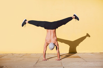 Man breakdancing in front of a yellow wall.