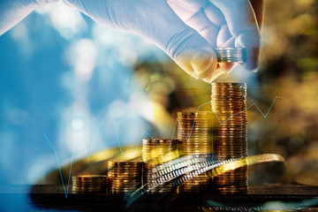 Double exposure of coin stacks with financial graph and copy space for business and financial concept. shallow focus.