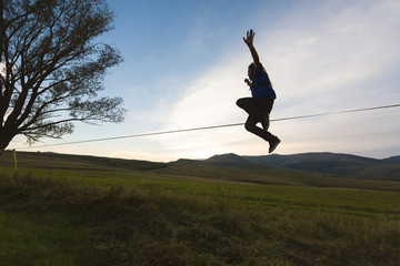 Young rebel man jumping off a tight rope outdoor in nature