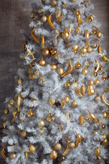 Golden christmas toys hanging on white artificial christmas tree