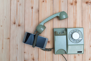 Retro rotary telephone or vintage phone with cable and new cell phone or smart phone on wood table, top view with copy space, technology progress concept.