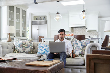 Hispanic businessman working on laptop in living room at home