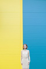 Young woman standing against a blue yellow wall