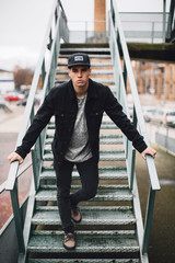 Portrait of a cool young man standing on urban stairs.
