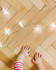 Crop baby hands on floor with garland