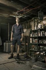 Portrait of Male Artist in Short Onesie in Studio Workshop Full of Spray Paint Cans