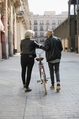 Active senior couple with a bicycle in the city