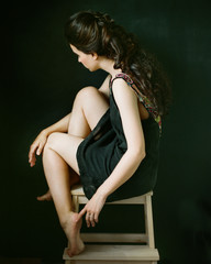 Woman in black dressing posing on chair